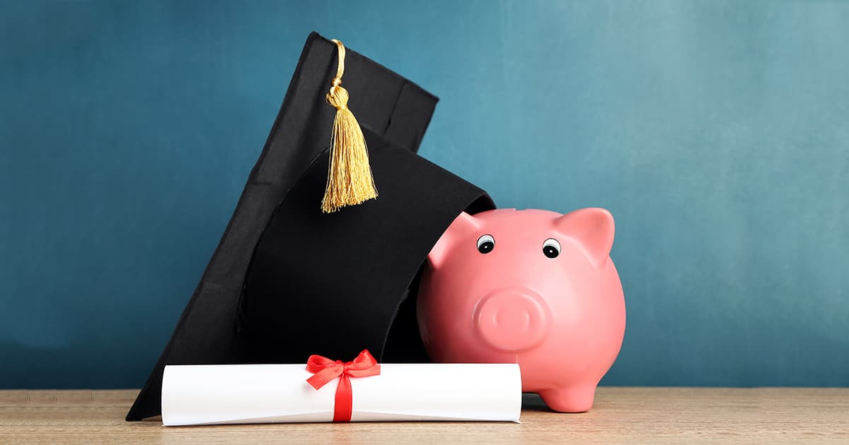 graduation mortarboard, diploma, and piggy bank